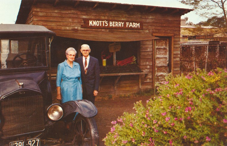 An elderly couple, Walter and Cordelia Knott, stand near a Model T and in front of a small wooden berry stand.