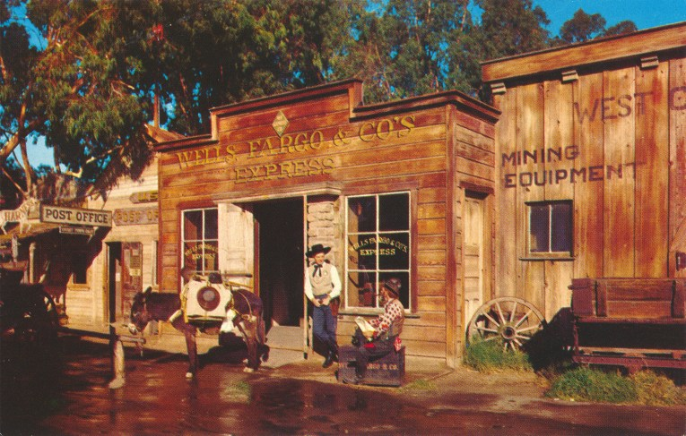 "Cowboys stand in front of a wooden building reading ""Wells Fargo & Co's Express"""