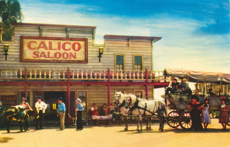 The Calico Saloon, a grey two story building with red trim. A stage coach pulled by two white horses stands out front.