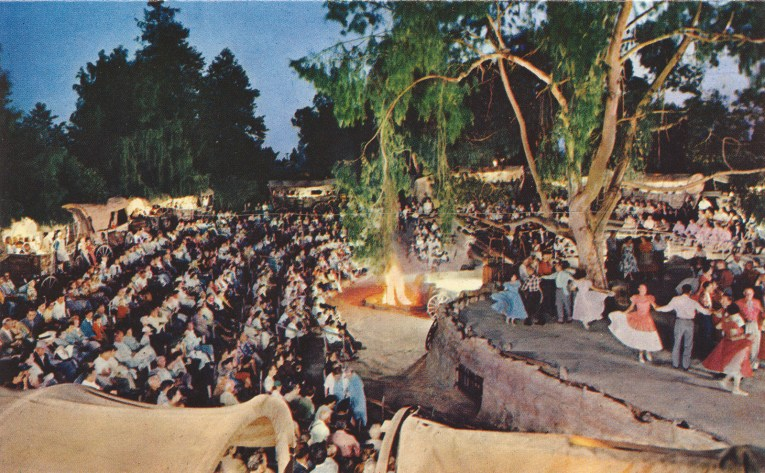 The Wagon Camp. Covered wagons with openings offer seating, along with regular benches for a stage where people dance.