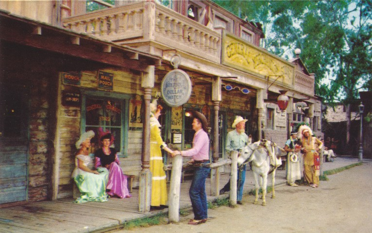 Men and women in old western attire stand outside the general store.