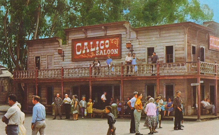 The Calico Saloon, a grey two story building with red trim. Guests stand outside and on the balcony.