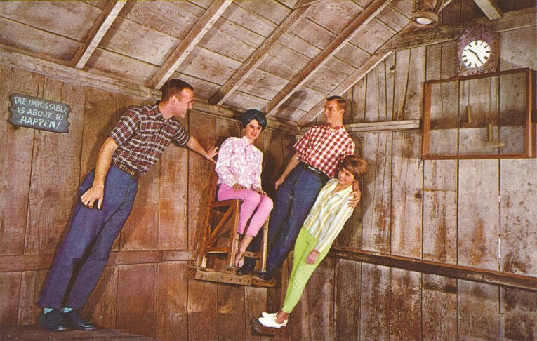 Inside the Haunted Shack. Guests stand on small ledges of all sorts of weird angles, a girl sits on a chair that is mounted to the wall.