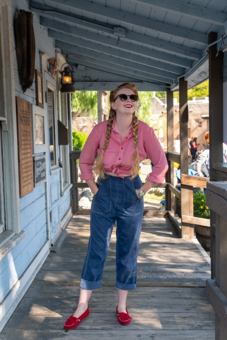 Myself standing on the porch of Judge Roy Bean's, a small western themed building, wearing a red and white gingham shirt, and blue jeans.