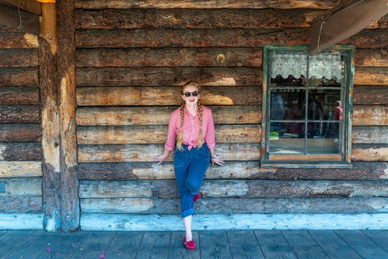 Myself standing in front of a building made of logs, wearing a red and white gingham shirt, and blue jeans.
