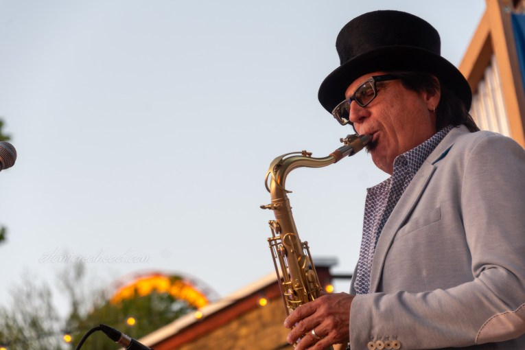 The saxophone player of the zydeco band blows notes while wearing a grey jacket and black top hat.