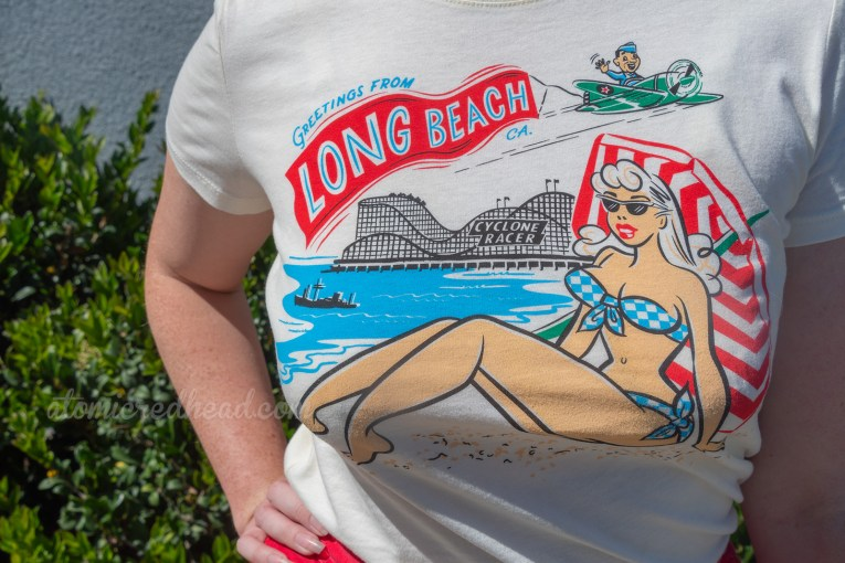 "Close up of my t-shirt, a female sunbather wear a blue and white bikini with the ocean and the Cyclone Racer behind her. An airman pilots a green plane with a red banner behind reading ""Greetings from Long Beach"""
