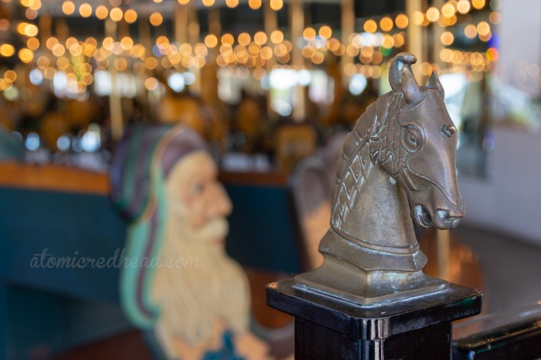 Closeup of a horse head that sits atop on the of the rails of the carousel.