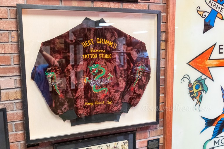 "A framed maroon jacket with a Chinese dragon embroidered on the back and sleeves. Yellow lettering reads ""Bert Grimm's Famous Tattoo Studio Long Beach, Cal."""