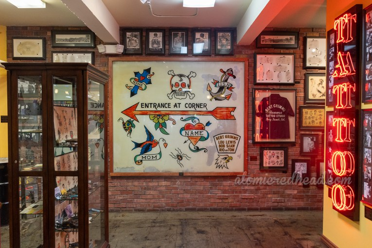 "Overall view of the museum portion of Outer Limits, including a massive hand-painted window with iconic tattoo images of skulls, crosses, hearts, anchor, text reads ""Entrance on Corner"""