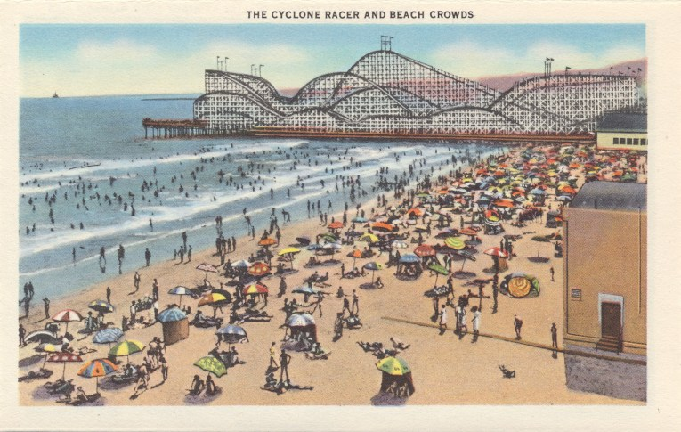 Postcard of the Cyclone Racer stretching over the ocean, sunbathers sit on the beach nearby.