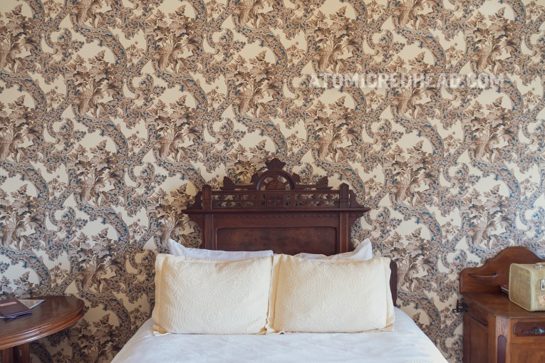 Interior of our room. An antique oak bed sits against a wall. Floral wallpaper in tan, blue, and white wraps around the room.