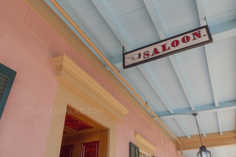 "A white sign with red letters reads ""Saloon"" with a hand painted pointed the way."