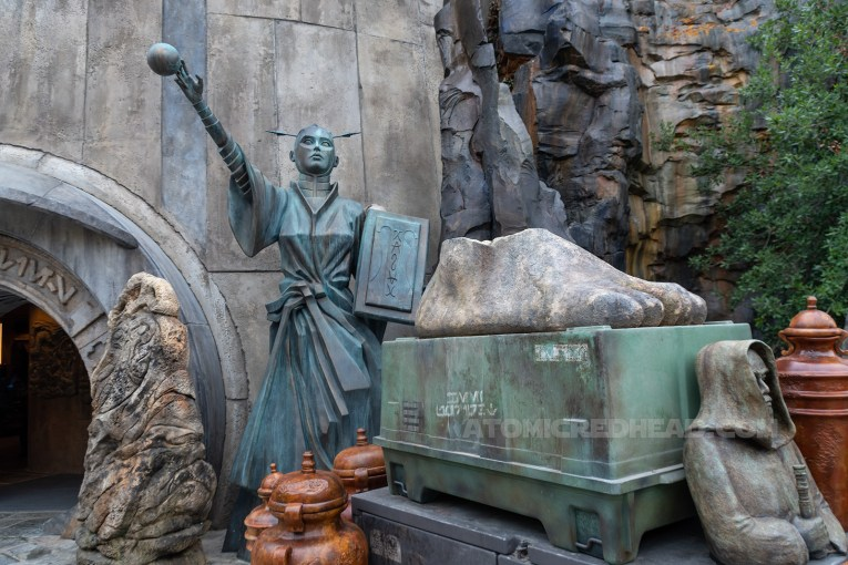 A statue of a woman holding a book and small ball stands guard next to a curved entry to a shop, near by cargo crates await to be unpacked.