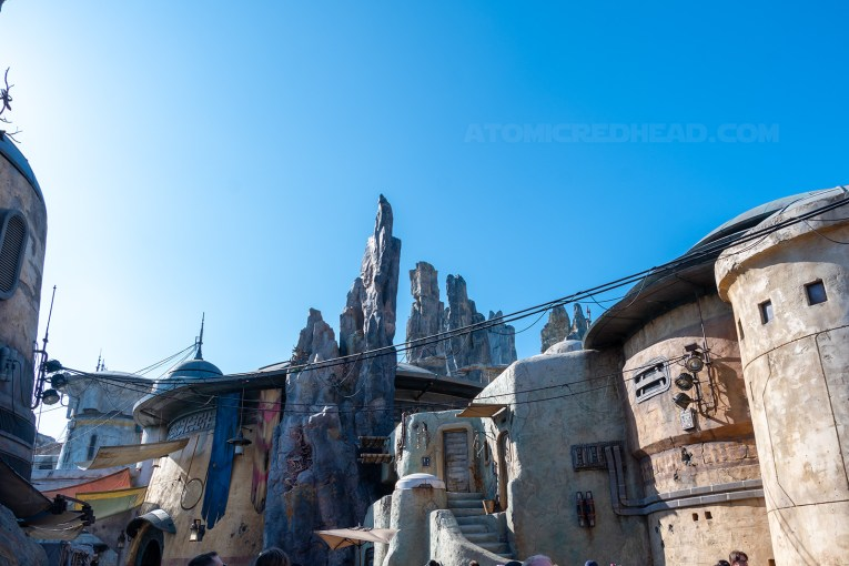 The round sided buildings of Batuu stand next to the craggy tall rocks in the background.