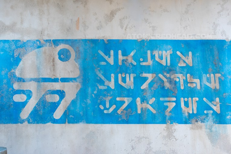 An image of a droid is painted on a wall with characters of Aurebesh, the writing system of the Star Wars universe, painted on a wall.