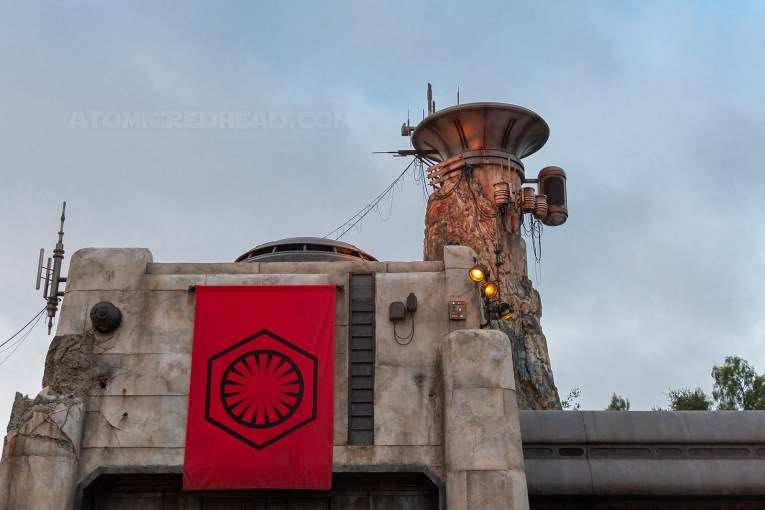 A red and black First Order banner hangs from a building, a tall look out tower stands behind it.