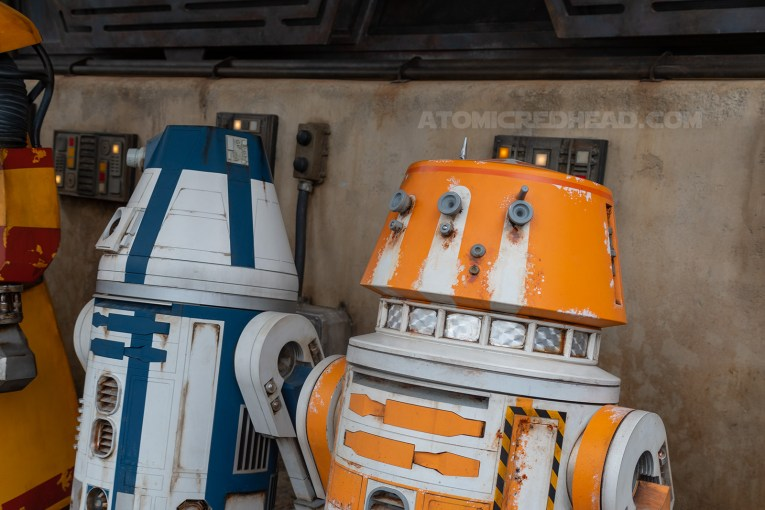 Full size droids outside the Droid Depot. One orange and white, another blue and white.