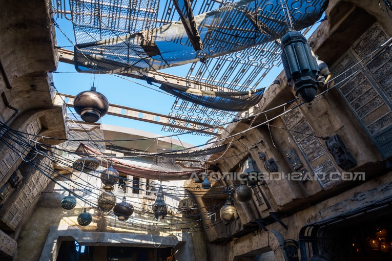 Above the outdoor marketplace of Batuu hang swaths of netting and eclectic metal lanterns.