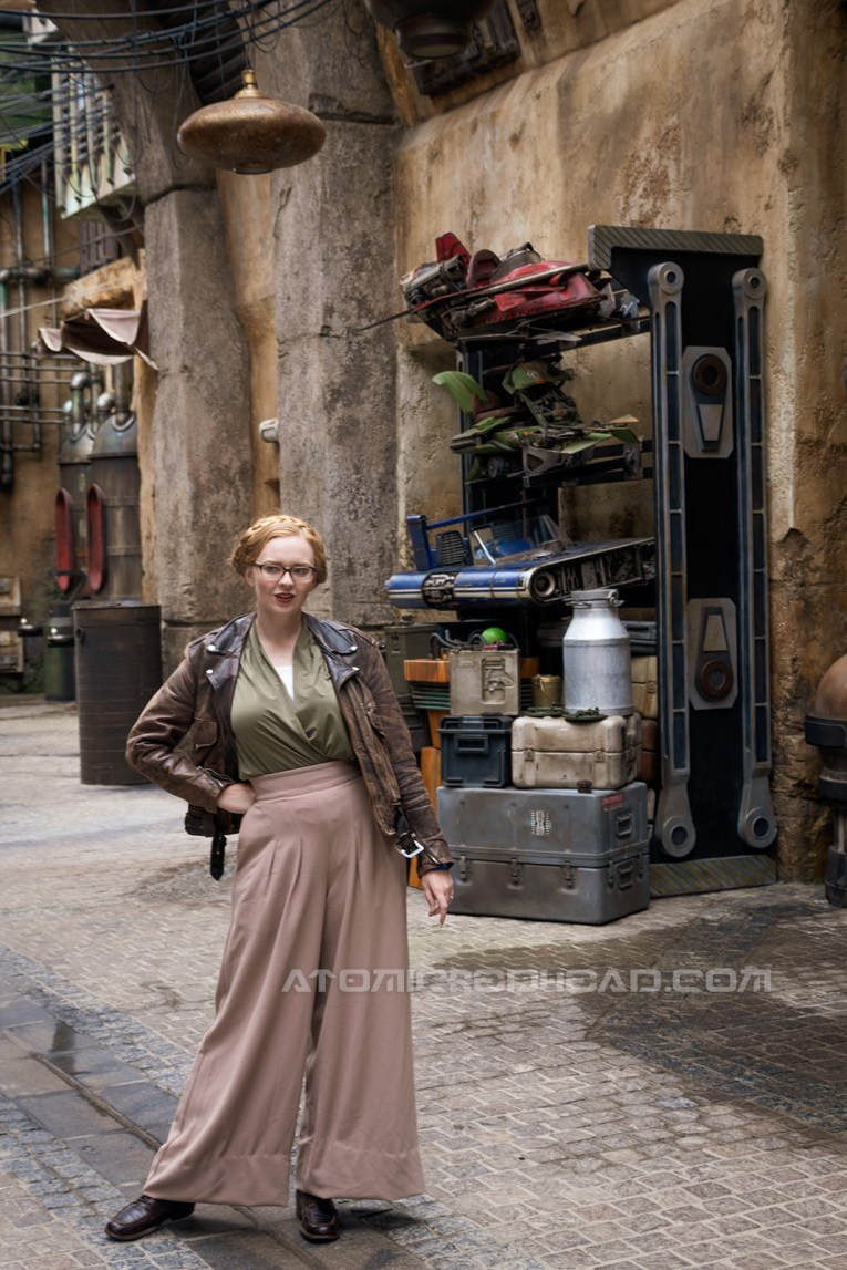 Myself standing in the marketplace of Batuu, wearing a dark brown motorcycle jacket, a green and white blouse, and tan wide leg slacks. Behind me small speeders for children sit on shelves.