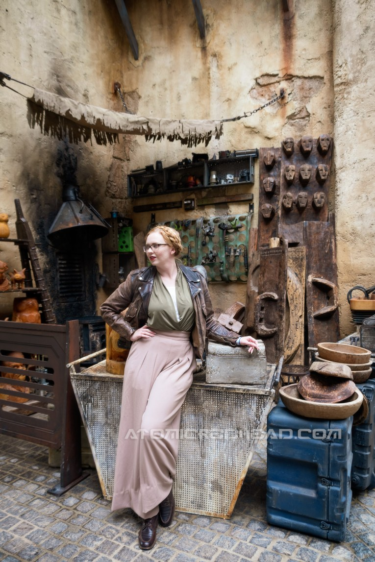 Myself standing in the marketplace of Batuu, wearing a dark brown motorcycle jacket, a green and white blouse, and tan wide leg slacks. Behind me a carving station with wooden figures of porgs, wookies and more.