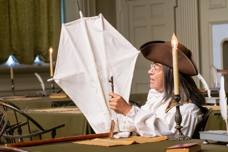 A Ben Franklin reenactor sits at a table holding a kite.