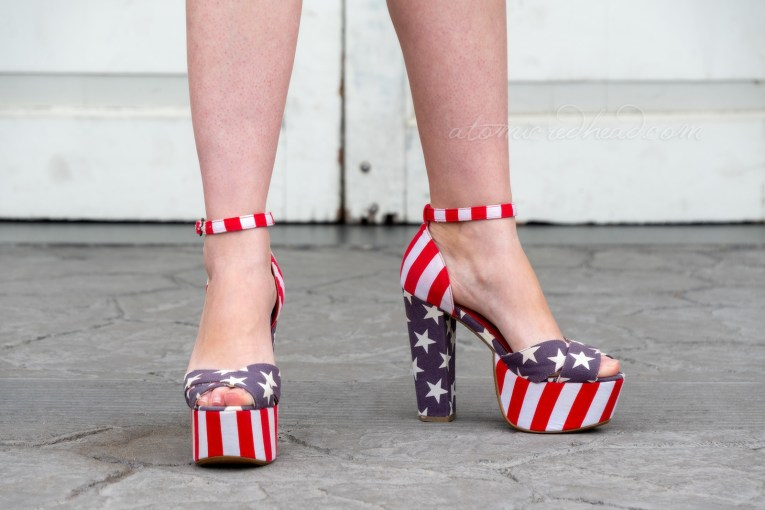 Close up of my shoes. The front platform features red and white stripes, the back heel is blue with white stars. The top part over the toes is blue with white stripes, and the heel and ankle strap are red and white stripes.