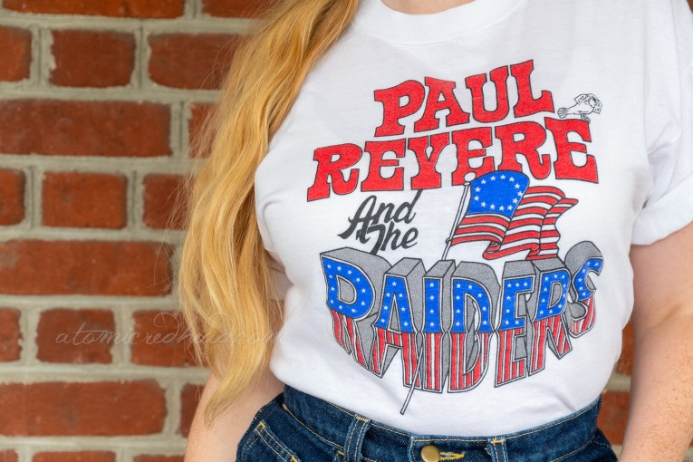 "Close-up of my t-shirt. Red letters read ""Paul Revere"" with black letters reading ""and the"" and then text emulating the flag reads ""Raiders"" the original version of the American flag juts from the ""Raiders"" portion. A small bird sits on the E of ""Revere"" and plugs his ears."