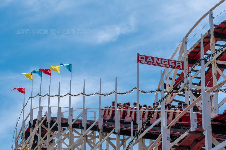 "Red cars make their way up one of the inclines on the Giant Dipper. Multi colored flags dot the incline. A sign reads ""Danger Keep arms inside car"""