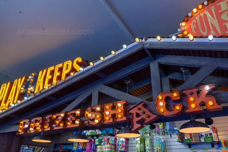 "Guests redeem their tickets at the prize counter, which features a small roof and lighted letters reading ""Prize Shack"" the ""A"" however appears as if it is falling off and is unlit."