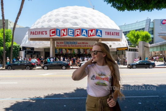 "Myself, wearing a white t-shirt reading ""Hollywood"" in red letters, and images of the Hollywood Bowl, Farmer's Market, Grauman's Chinese Theater, and the Capitol Records Building, standing in front of the white dome that is the Cinerama building. A red, white, and blue sign reads ""Pacific Cinerama Theatre."