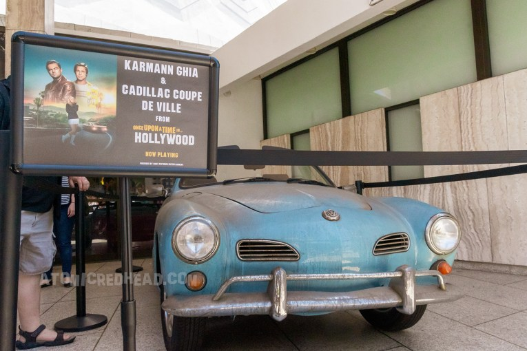 A blue Karmann Ghia sits in front of the white marble box office, which was used in the film.