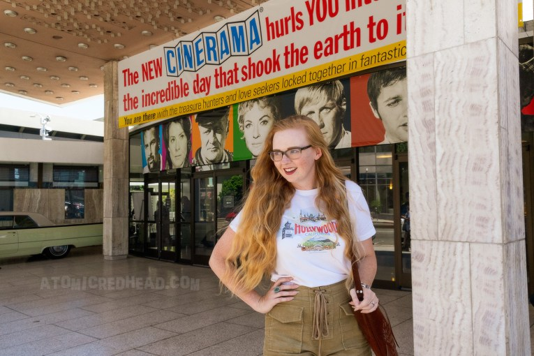 "Myself, wearing a white t-shirt reading ""Hollywood"" in red letters, and images of the Hollywood Bowl, Farmer's Market, Grauman's Chinese Theater, and the Capitol Records Building, and tan lace up shorts, leaning against a white marble post near the front of the theatre."