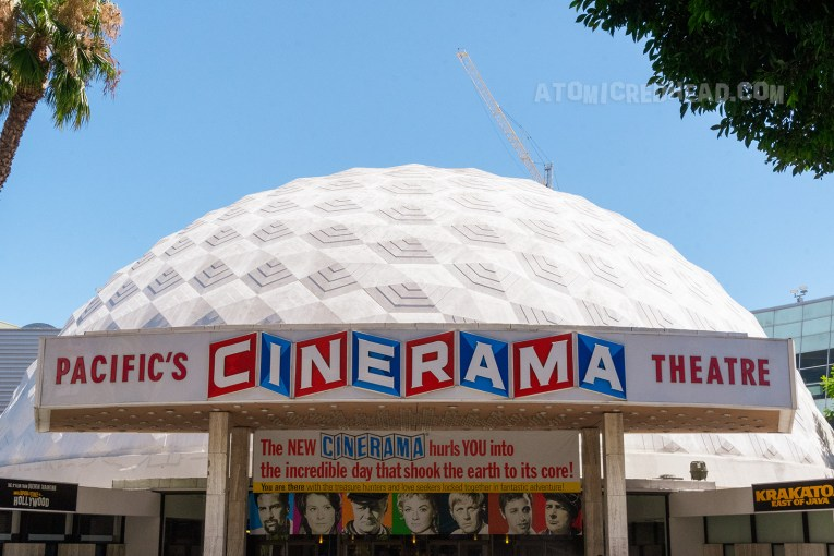 "The Cinerama Dome, a white dome rises from the street, with a slightly textured surface. A red, white, and blue sign reads ""Pacific Cinerama Theatre"""