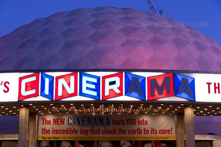 "The Dome at sunset, a red, white, and blue sign reads ""Pacific Cinerama Dome"" The white dome is lit with red lights."