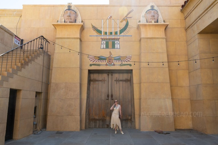 Myself standing in front of a massive pair of wood doors, wearing a sleeveless cream lace dress, a blue scarf with white hieroglyphs, and a blue scarab necklace. Above the two doors of painted hieroglyphs