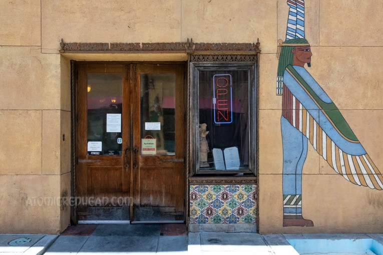 A wooden door and window with tile work below it enters into the neighboring restaurant of Pig n Whistle. Painted to the right is a mural of winged Egyptian gods.