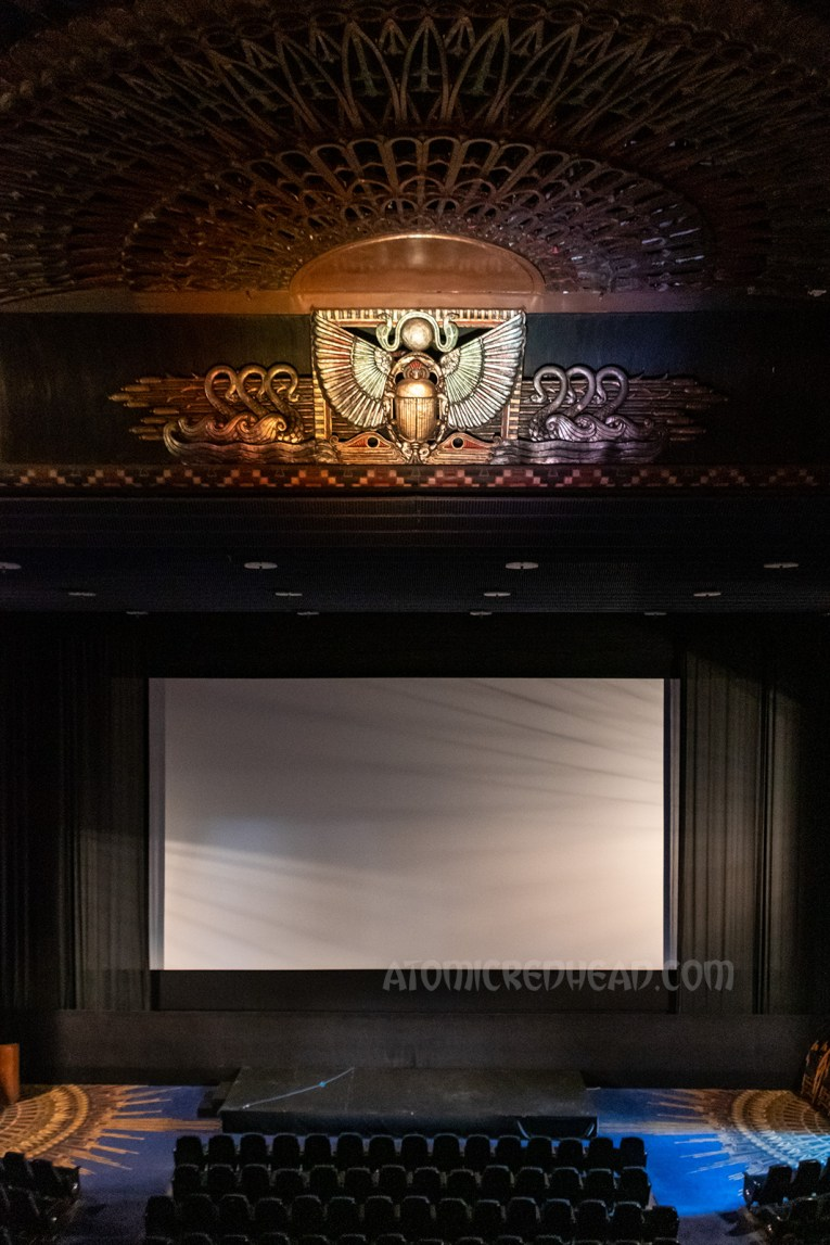 Image of the movie screen with the sun and scarab above.