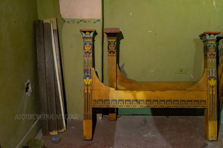 Rails for what may have been a bench, are painted in the same yellow paint as the vanity, and also feature an Egyptian motif.