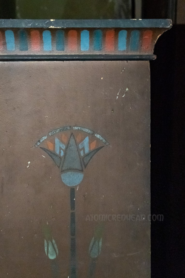 Close-up of the side of a dresser that features a lotus design.