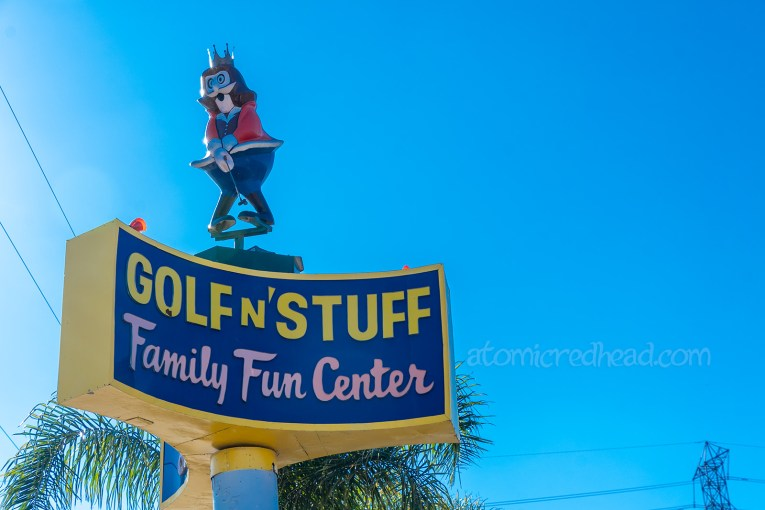 "Sign for Golf N' Stuff, a blue sign with yellow lettering spelling ""Golf N' Stuff"" with pale pink lettering below spelling ""Family Fun Center"" atop the sign is a cartoony king in red and blue clothes with a golf club."