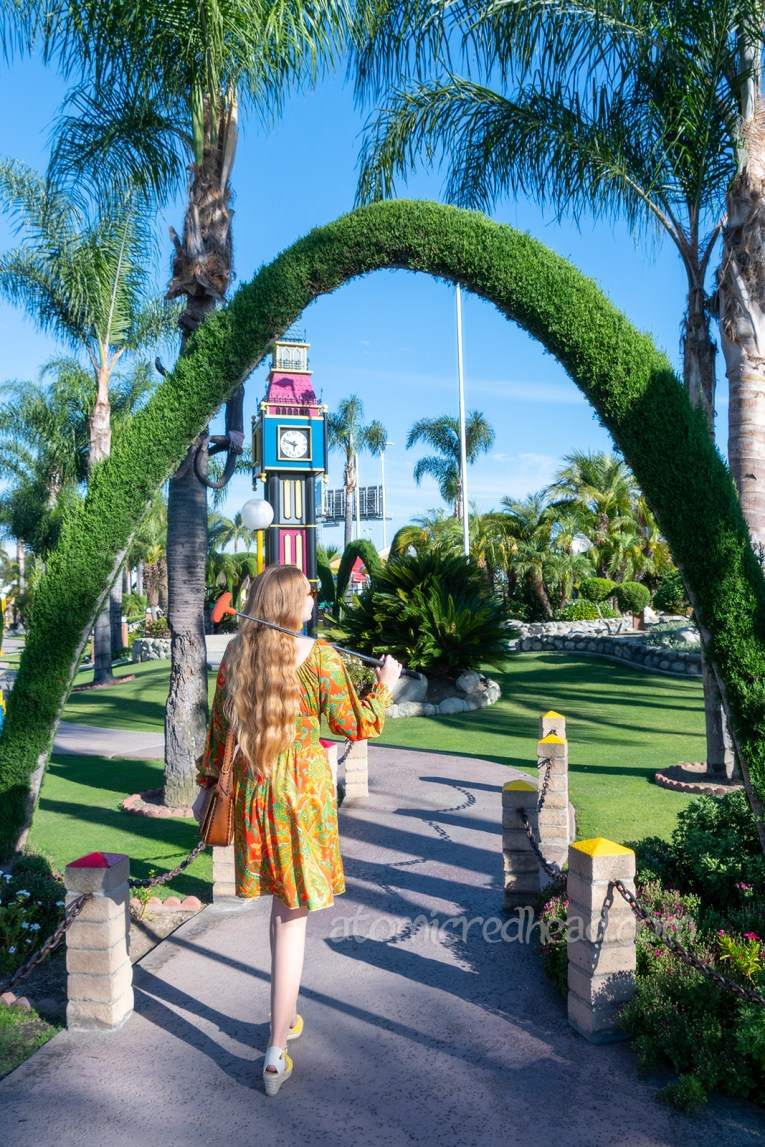 Myself, wearing a long sleeve, mini dress of orange, yellow, and green in a paisley print, walking into the golf course. Various hedges form arches over the walkways. A brightly colored fanciful version of Big Ben stands in the distance.