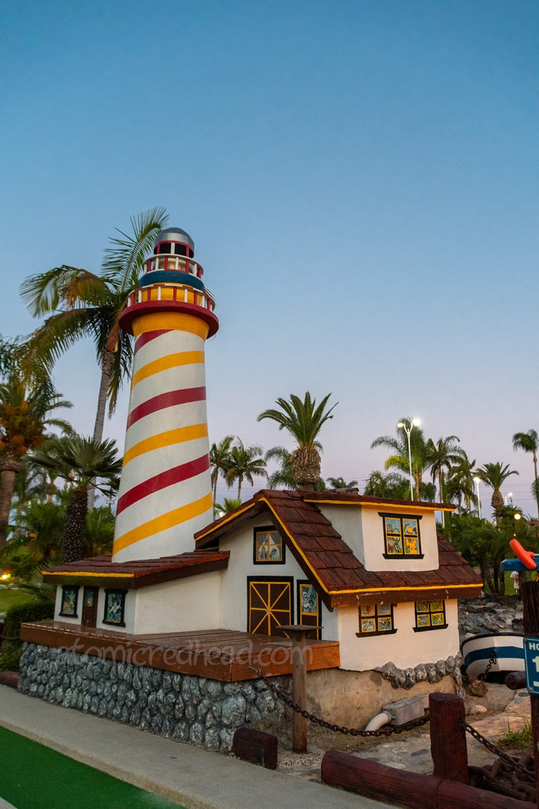 A miniature light house painted white, red, and yellow.