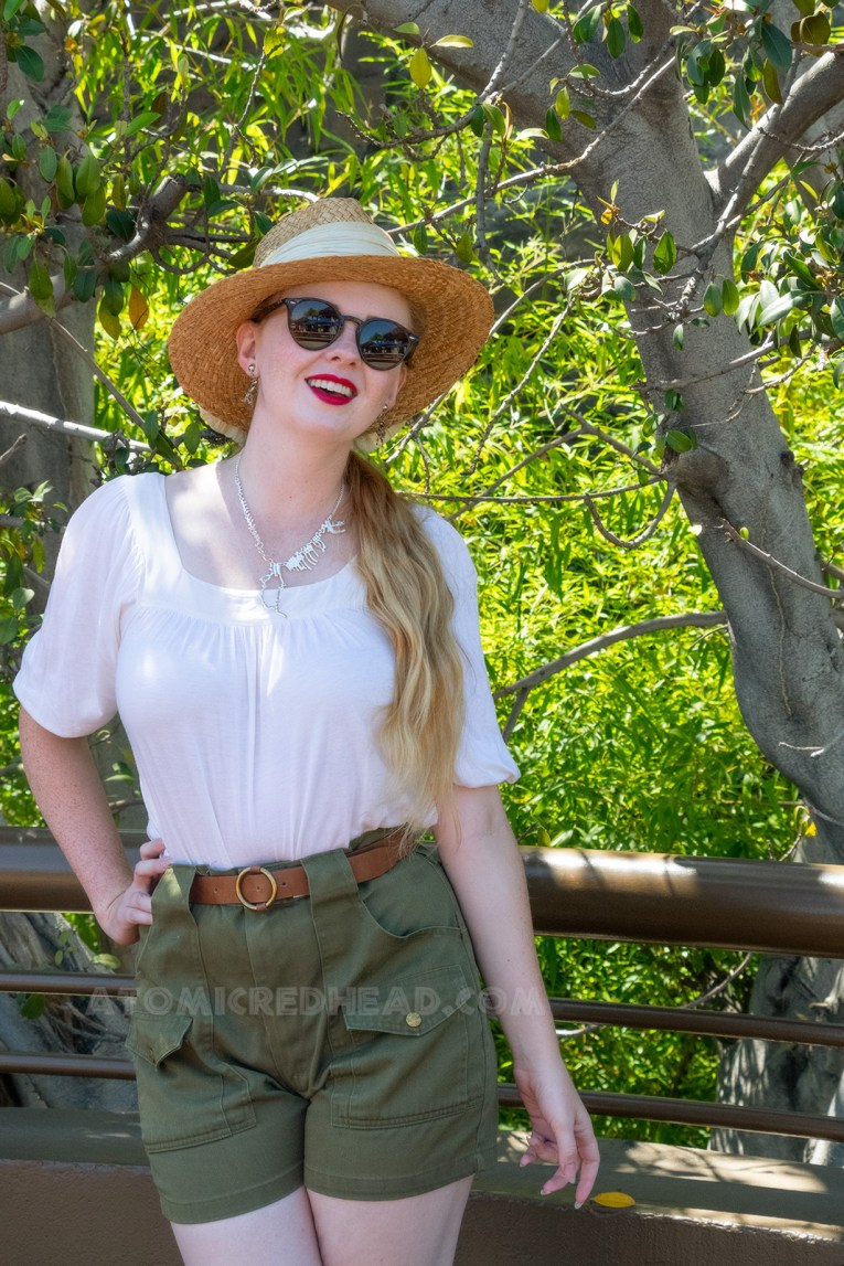 Standing on an upper balcony near the Jurassic World ride, wearing a straw hat with white fabric around, a white peasant top, and olive green shorts, and a silver necklace of a T-Rex skeleton.