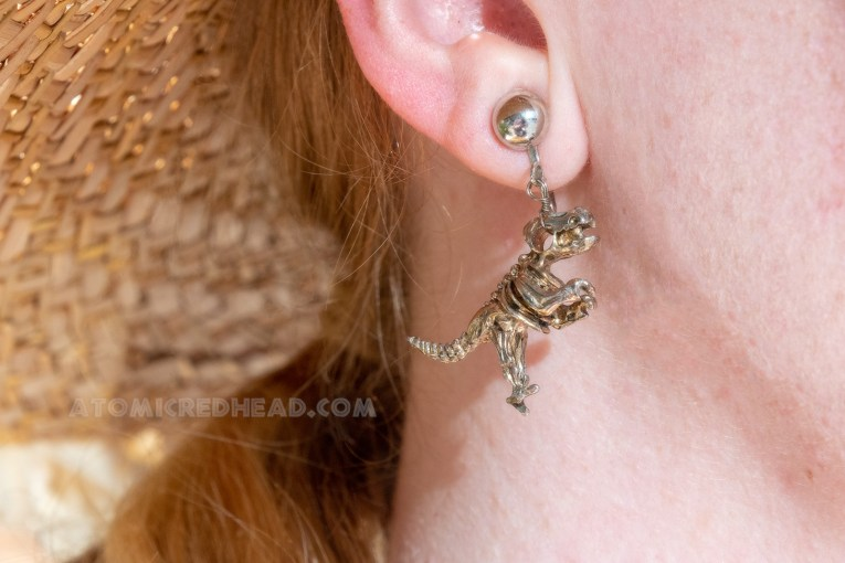 Close-up of my earrings, which are T-rex skeletons.
