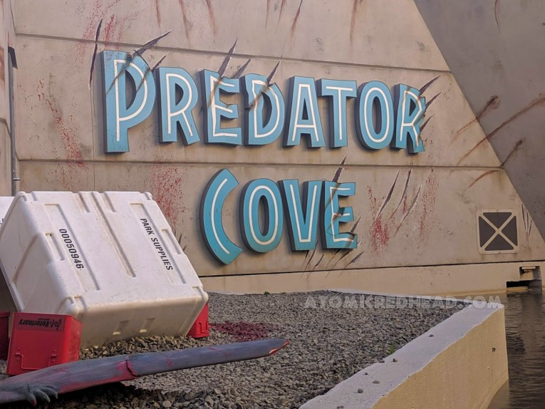 "Signage for ""Predator Cove"" is slashed with blood on the wall, implying the terrifying new Indominus rex has escaped."