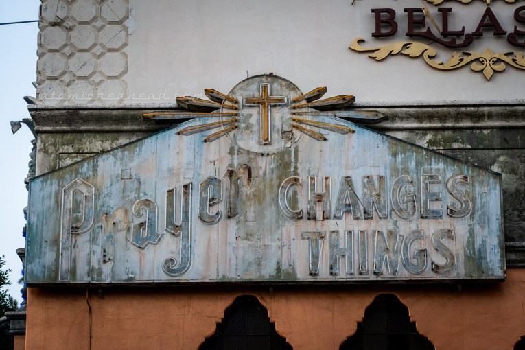 "An unlit neon sign with fading paint reads ""Prayer changes things"" with a cross above."