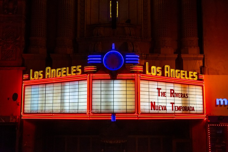 "A marquee reads ""Los Angeles"" on both sides in yellow neon. Red neon frames the white marquee area."