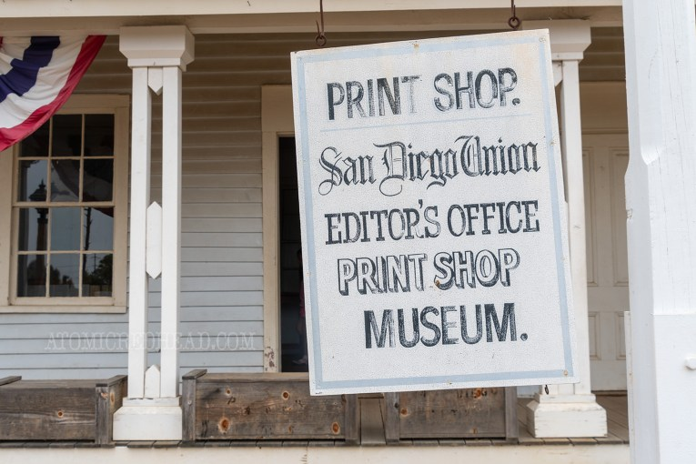 "A hanging white sign reads ""Print Shop. San Diego Union Editor's Office Print Shop Museum"""