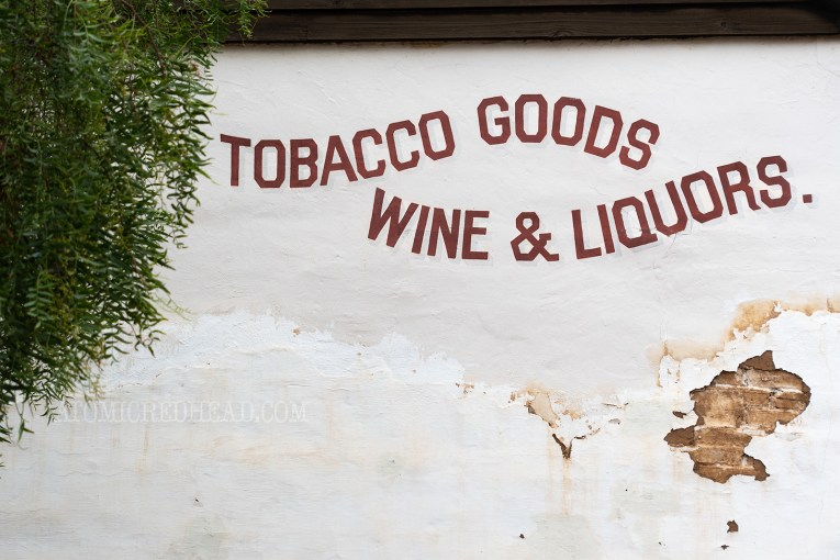 "An old adobe wall features waving text reading ""Tobacco Goods Wine & Liquor"""